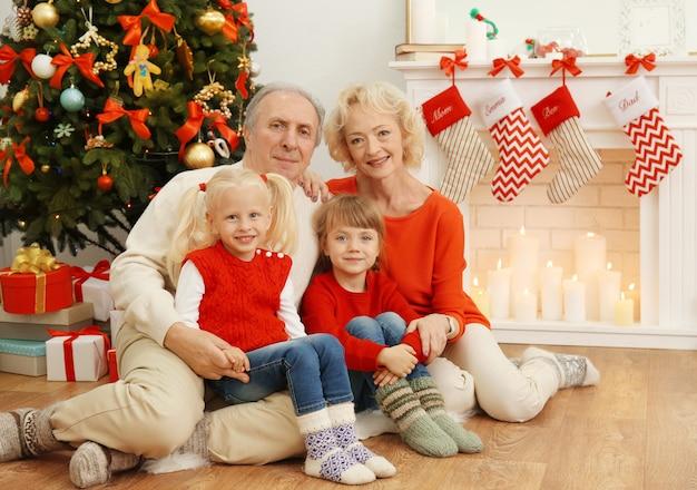 Starsze małżeństwo z wnuczkami siedzą przy kominku udekorowanym na boże narodzenie