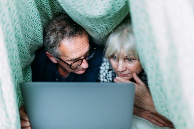 Starsze osoby dobierają się wpólnie w łóżku z laptopem