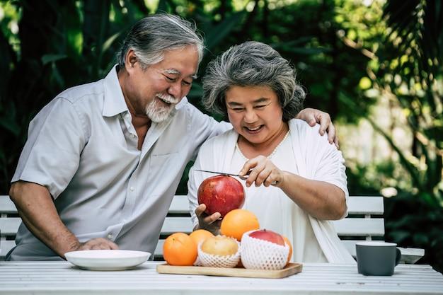 Starsze pary bawiące się i jedzące owoce