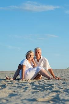 Starsze pary na plaży cieszą się morską bryzą