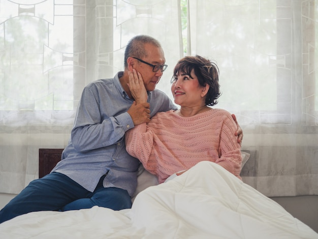 Starsze pary siedzą i odpoczywają w łóżku