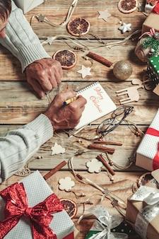 Starsze ręce seniora pisanie listu do świętego mikołaja lub wesołych świąt
