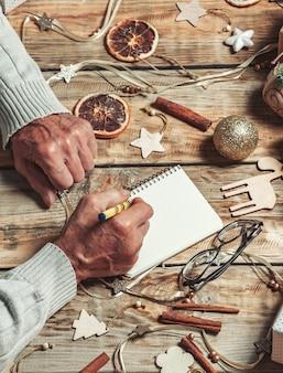 Starsze ręce seniorów pisanie listu do listy zakupów świętego mikołaja lub boże narodzenie