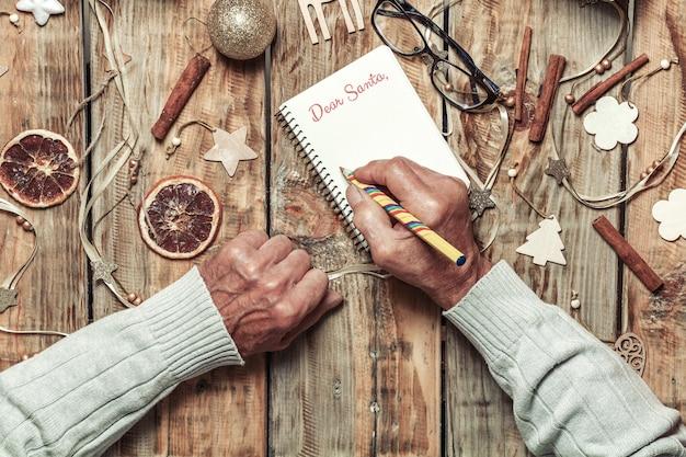 Starsze ręce seniorów pisanie listu do santa lub christmas shoppi