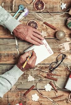 Starsze ręce seniorów pisze plan na następny rok lub list do mikołaja