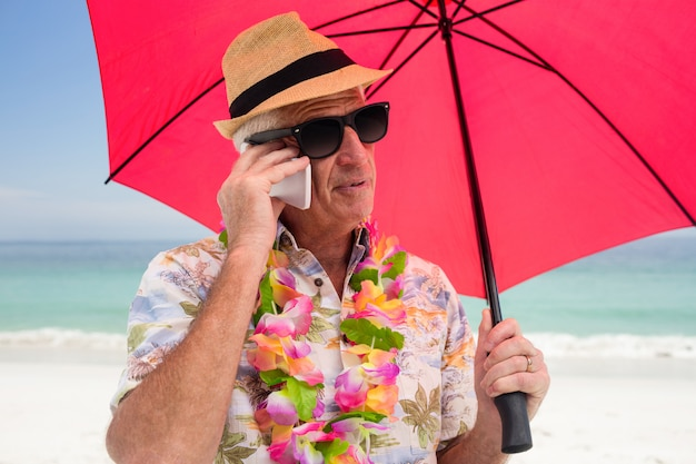 Starszego mężczyzna mienia parasol podczas gdy opowiadający na telefonie