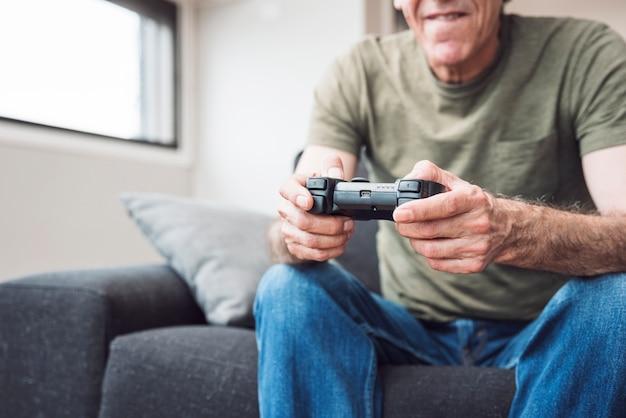 Starszego mężczyzna obsiadanie na kanapie bawić się wideo grę w domu
