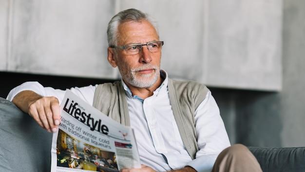 Starszego mężczyzna obsiadanie na kanapie mienia gazecie w jego ręce patrzeje daleko od