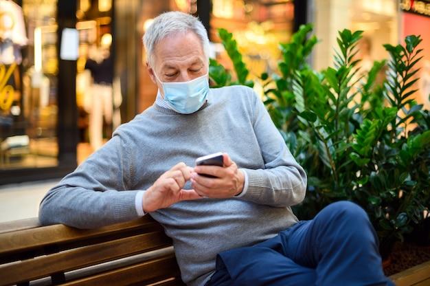 Starszego mężczyzna obsiadanie na ławce i używać smartphone w centrum handlowym jest ubranym maskę