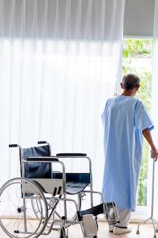 Starszego mężczyzna pacjent z chodzącym kijem w sala szpitalnej.