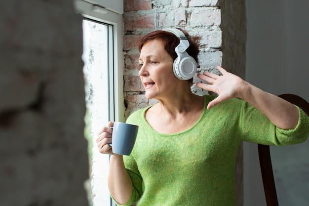 Starszej kobiety słuchająca muzyka i patrzeć na okno