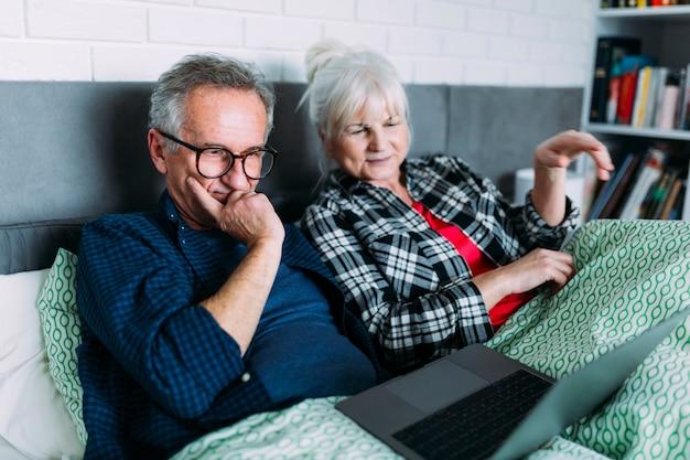 Starszej osoby para w łóżku patrzeje laptop