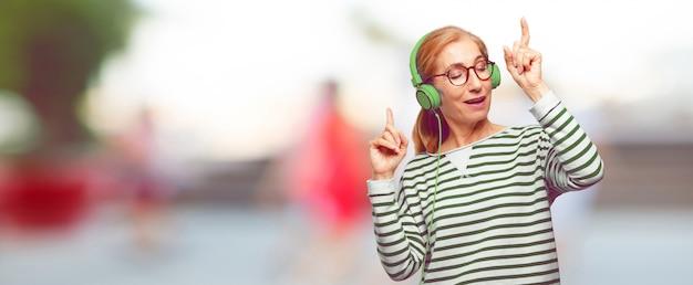 Starszej pięknej kobiety słuchająca muzyka z hełmofony