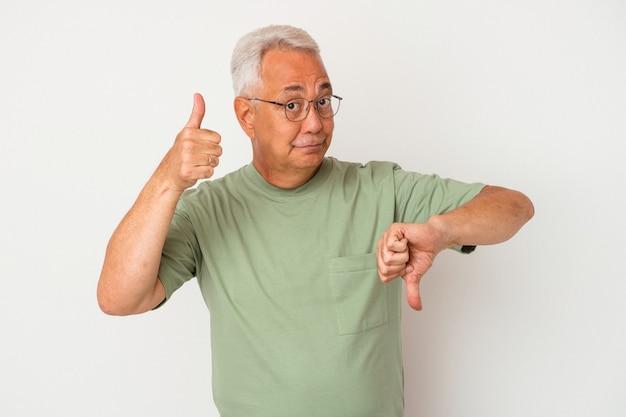 Starszy amerykanin na białym tle na białym tle pokazując kciuk w górę i kciuk w dół, trudny wybór koncepcji