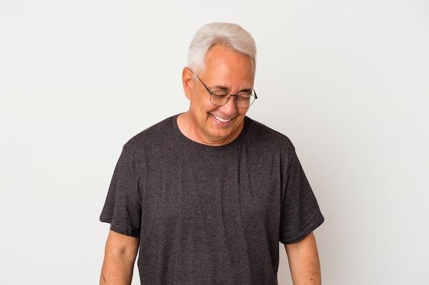 Starszy amerykanin na białym tle śmieje się i zamyka oczy, czuje się zrelaksowany i szczęśliwy.