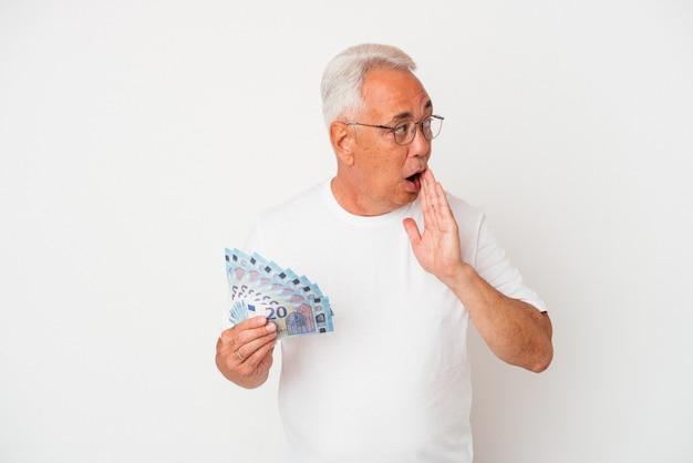 Starszy amerykanin trzymający rachunek na białym tle mówi tajne gorące wiadomości o hamowaniu i patrzy na bok