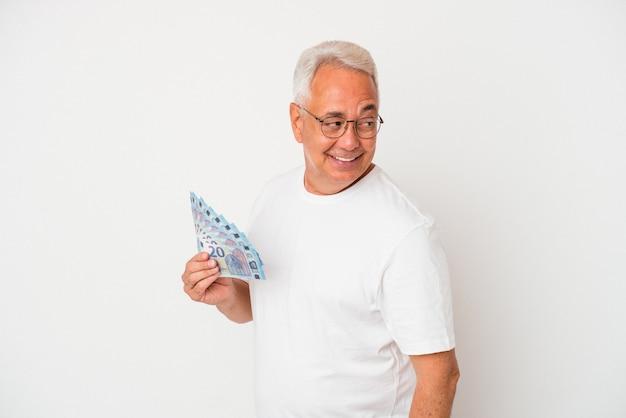 Starszy amerykanin trzymający rachunek na białym tle wygląda na bok uśmiechnięty, wesoły i przyjemny.