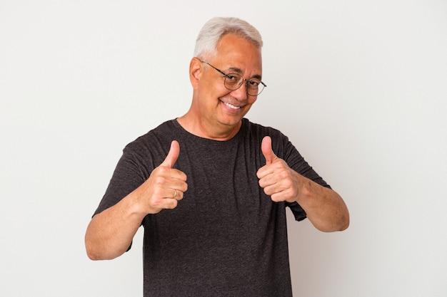 Starszy amerykański mężczyzna na białym tle podnosząc oba kciuki do góry, uśmiechnięty i pewny siebie.