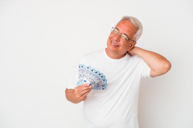 Starszy amerykański mężczyzna trzyma rachunek na białym tle dotykając tyłu głowy, myśląc i dokonując wyboru.