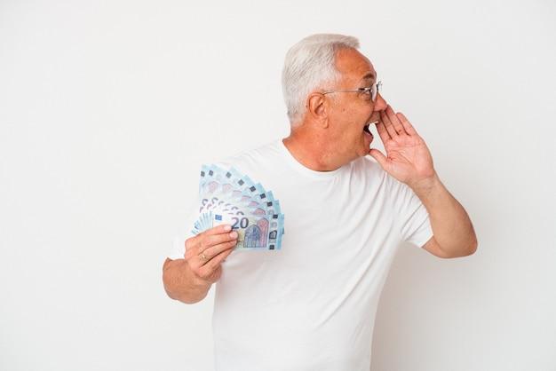 Starszy amerykański mężczyzna trzyma rachunek na białym tle na białym tle krzycząc i trzymając dłoń w pobliżu otwartych ust.