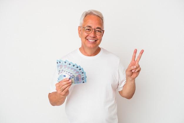 Starszy amerykański mężczyzna trzymający rachunek na białym tle radosny i beztroski pokazujący symbol pokoju palcami.