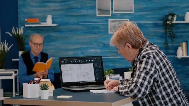 Starszy architekt analizujący cyfrowy prototyp z planami z laptopa