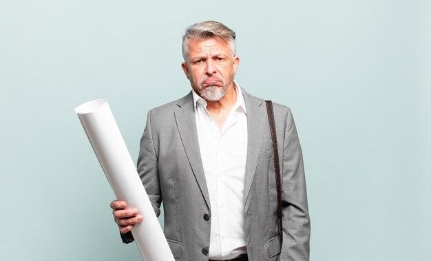 Starszy architekt czuje się smutny i marudny z nieszczęśliwym spojrzeniem, płacze z negatywnym i sfrustrowanym nastawieniem
