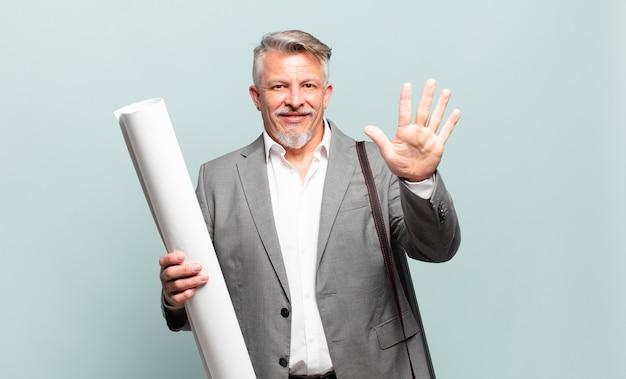 Starszy architekt uśmiecha się i wygląda przyjaźnie, pokazując cyfrę piątą lub piątą z ręką do przodu, odliczając w dół