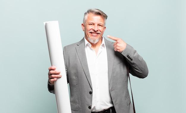 Starszy architekt uśmiechnięty pewnie wskazujący na swój szeroki uśmiech, pozytywna, zrelaksowana, usatysfakcjonowana postawa