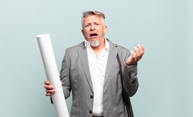 Starszy architekt wyglądający na zdesperowanego i sfrustrowanego, zestresowanego, nieszczęśliwego i zirytowanego, krzyczącego i krzyczącego