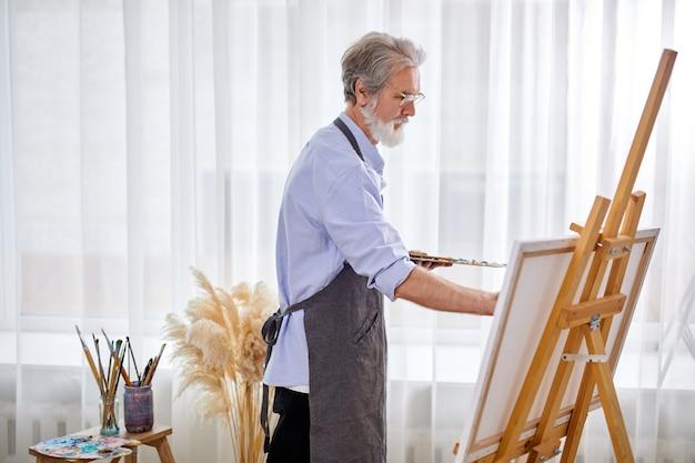 Starszy artysta skupiony na malowaniu, kaukaski mężczyzna w fartuchu jest pogrążony w tworzeniu sztuki