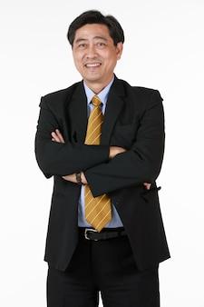 Starszy azjatycki biznesmen stojący z rękami skrzyżowanymi. zdjąć okulary uśmiech spojrzeć na aparat. znaki sukcesu bankier, biznesmen, prawnik. gest bardziej zrelaksowany i szczęśliwą twarz.