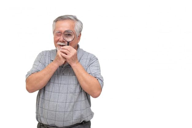 Starszy azjatycki mężczyzna patrzeje przez powiększać - szkło i ono uśmiecha się odizolowywającymi na biel ścianie