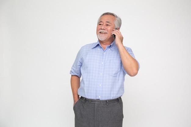 Starszy azjatycki mężczyzna rozmawia przez telefon komórkowy na białym tle
