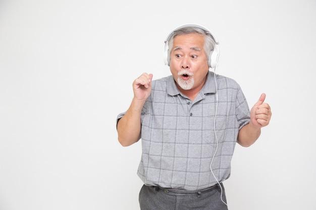Starszy azjatycki mężczyzna słucha ulubionej muzyki przez słuchawki na białym tle
