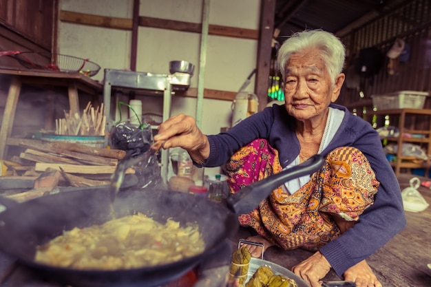 Starszy azjatykci kobieta szefa kuchni kucharz w kuchni, tradycyjnej w tajlandia