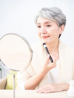 Starszy azjatykcia kobieta nakłada fundament na jej policzek za pomocą pędzla do makijażu, siedząc samotnie przed lustrem.