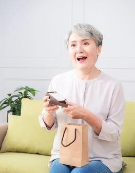 Starszy azjatykcia kobieta otrzymuje prezent z perłowego naszyjnika.