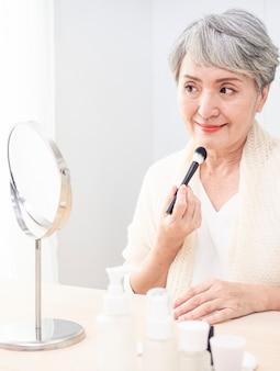 Starszy azjatykcia kobieta, stosując fundament do jej policzka za pomocą pędzla do makijażu, siedząc samotnie przed lustrem.