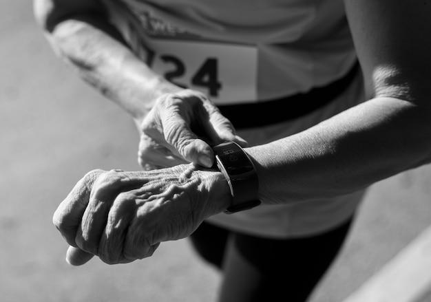 Starszy biegacz korzystający z urządzenia do monitorowania kondycji