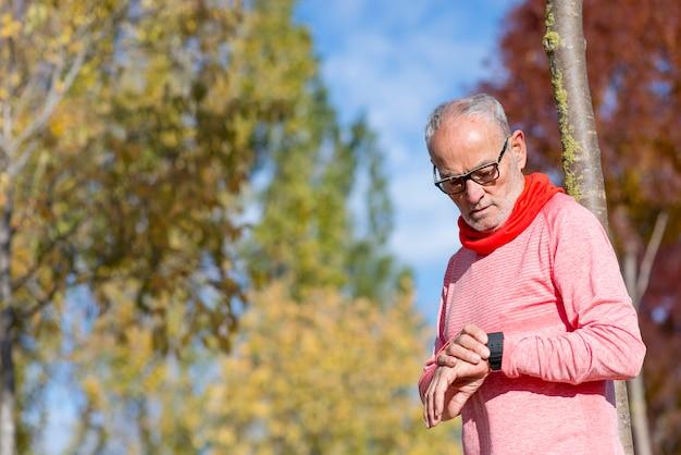 Starszy biegacz mężczyzna odpoczywa przy parkiem podczas gdy monitorujący jego ćwiczenie