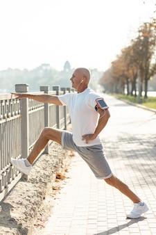 Starszy biegacz rozciąganie przy ogrodzeniem