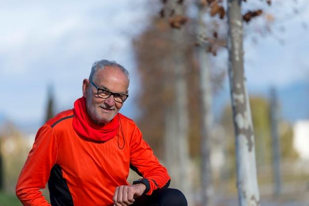 Starszy biegacza mężczyzna odpoczywa przy parkiem podczas gdy monitorujący jego ćwiczenie