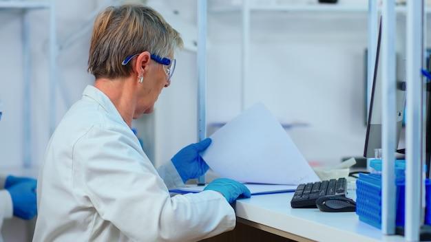 Starszy biochemik piszący i patrzący na komputer analizujący raporty medyczne w nowocześnie wyposażonym laboratorium. wieloetniczne materiały badające ewolucję szczepionek przy użyciu zaawansowanych technologicznie metod leczenia covid19