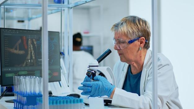 Starszy biotechnolog, naukowiec prowadzący badania w nowocześnie wyposażonym laboratorium. wieloetniczny zespół badający ewolucję wirusa przy użyciu zaawansowanych technologii do badań naukowych nad opracowaniem szczepionki przeciwko covid19