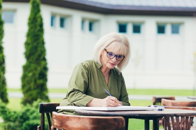 Starszy biznes kobieta siedzi na krześle