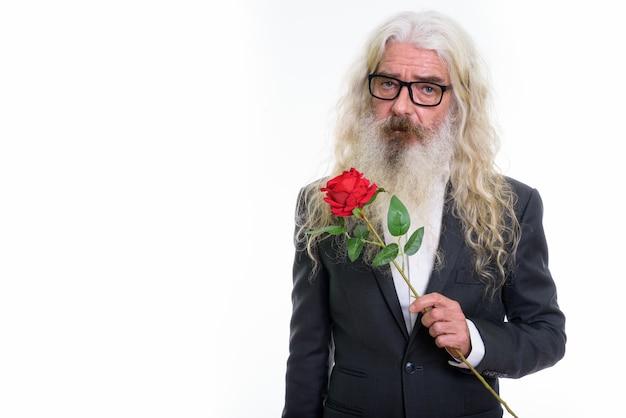 Starszy biznesmen brodaty gospodarstwa czerwona róża