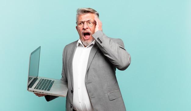 Starszy biznesmen czuje się szczęśliwy, podekscytowany i zaskoczony, patrząc w bok z obiema rękami na twarzy