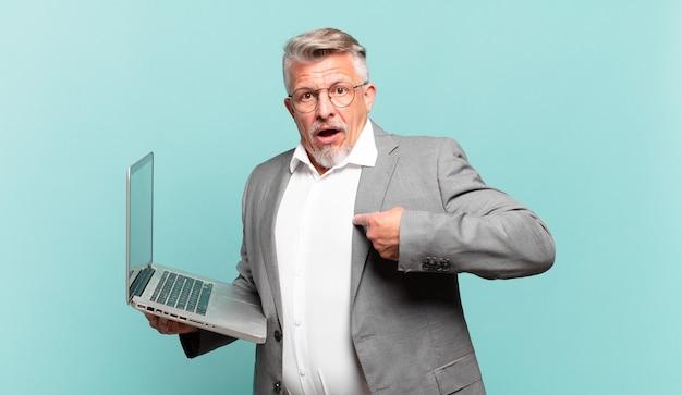 Starszy biznesmen czuje się szczęśliwy, zaskoczony i dumny, wskazując na siebie z podekscytowanym, zdumionym spojrzeniem