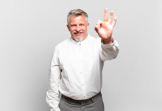 Starszy biznesmen czuje się szczęśliwy, zrelaksowany i zadowolony, okazując aprobatę dobrym gestem, uśmiechając się